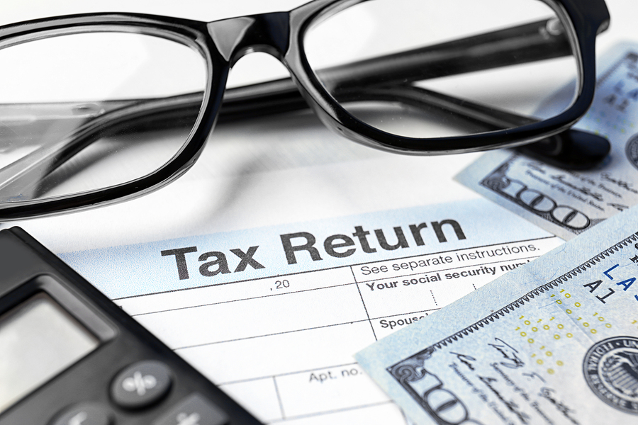 Tax return documents with a pair of glasses and some money.