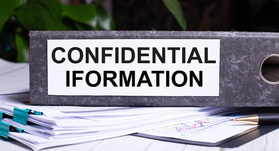 CONFIDENTIAL INFORMATION is written on a gray file folder next to documents. Business data security concept